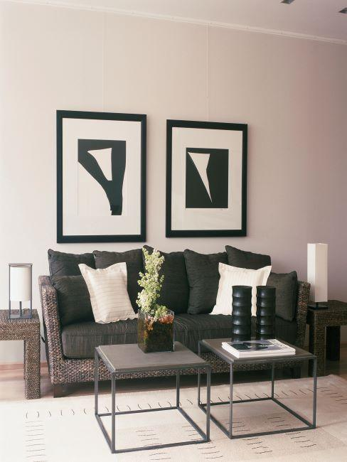 salon moderne, canapé noir en cannage, deux tables basses jumelles, deux grands cadres noir et blanc sur le mur