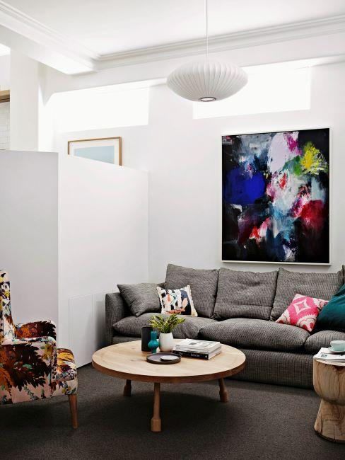 salon moderne avec canapé gris, table basse ronde, un grand tableau multicolore sur le mur et fauteuil multicolore