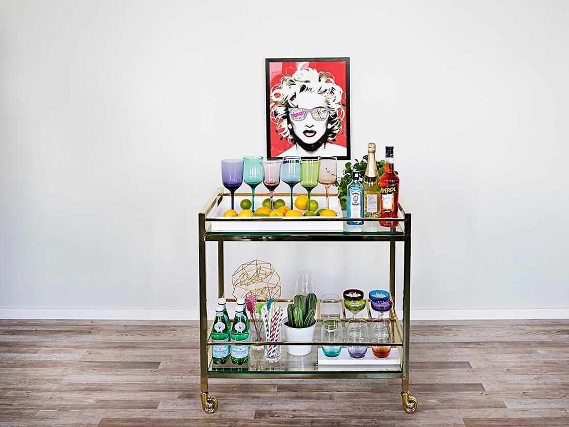 Chariot bar à la maison avec verres colorés et affiche murale marilyn monroe