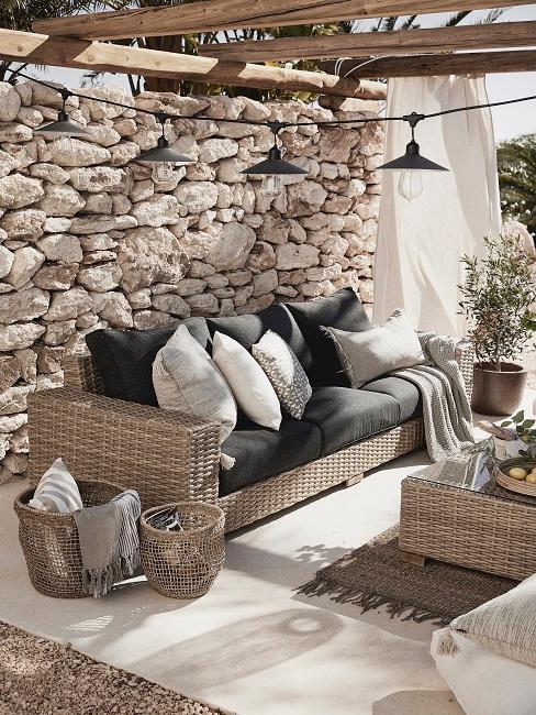 déco outdoor, décoraiton extérieure, mur en galets, canapé outdoor en rotin synthétique, coussins d'extérieur