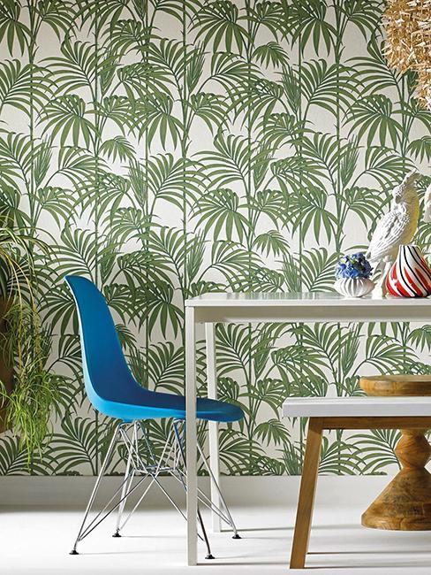 Table avec chaise bleue et tapisserie tropicale