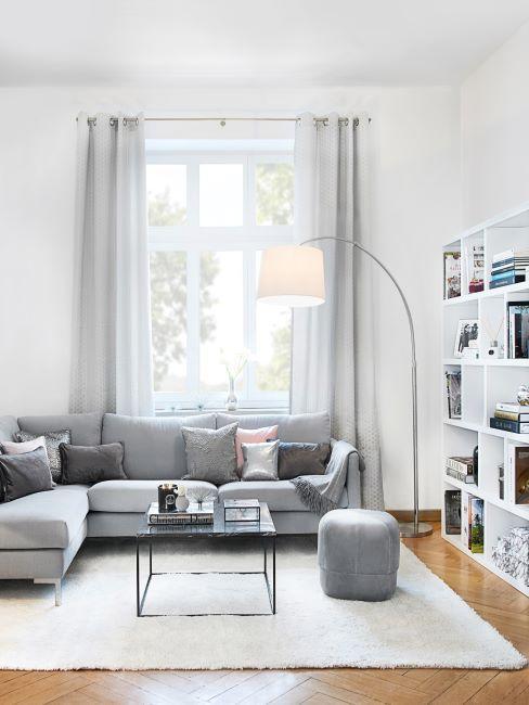 vue d un sejour avec un large canape d angle gris clair, murs blancs, tapis blanc , rideaux gris