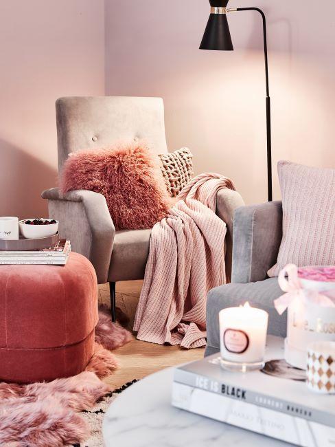 fauteuil clair couvert de plaid rose et décoré d'un coussin rose foncé à longs poils, lampadaire, bougies parfumées posées sur la table basse, ambiance cocooning