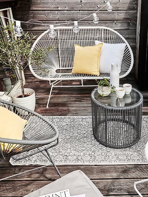 balcon avec salon de jardin gris, tapis et guilande lumineuse