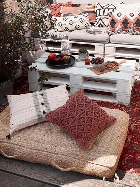 extérieur avec coussin de sol en jute, coussins décoratifs et table basse en palette