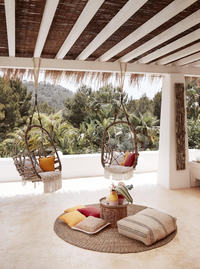 fauteuils suspendus, coussins au sol et tapis en jute sur une terrasse couverte,