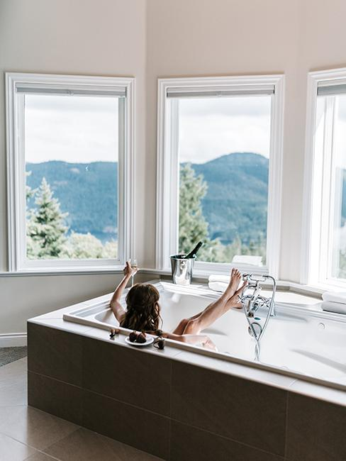 Salle de bain lumineuse avec baignoire et grandes fenêres