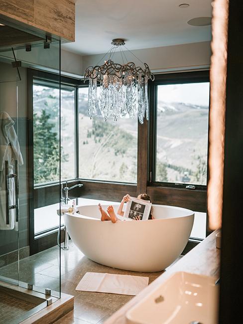 Salle de bain lumineuse avec baignoire blanche, douche et lustre