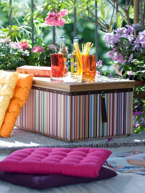 grande boite en guise d une table de fete, coussin de sol, verres a cocktail avec des pailles, fete a l exterieur