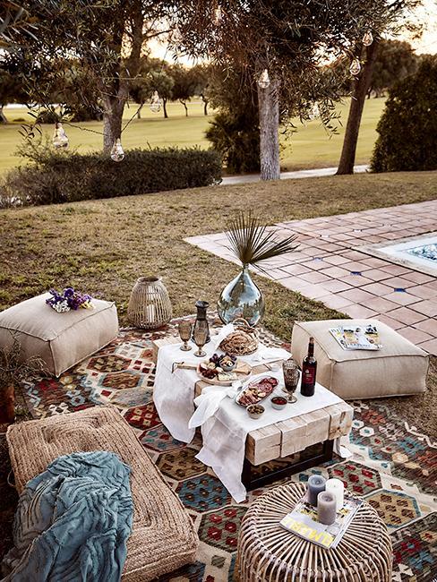 pique nique au fond du jarin avec grand tapis vintage, poufs et coussins, guirlandes lumineuses dans un arbre