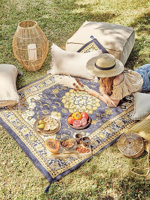 pique-nique dans l'herbe avec fille sur un tapis vintage entrain de lire, lanterne en bambou et coussins de sol
