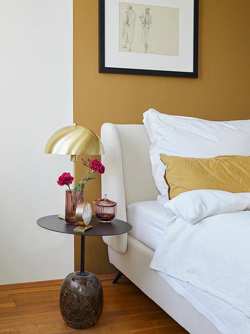 lampe de chevet en laiton dans une chambre avec un mur jaune et blanc
