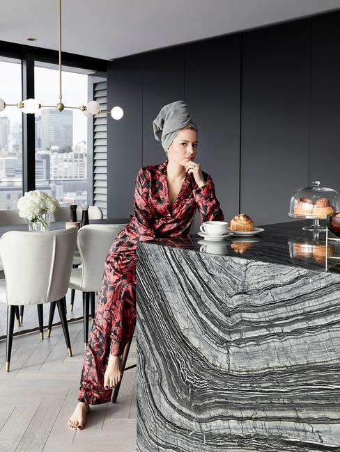 plan de travail de cuisine en marbre gris et femme en pyjama satin rouge