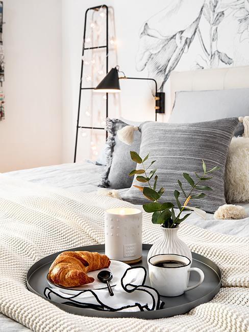 Plateau de petit déjeuner avec croissant, tasse de café et verre de lait placé sur un lit