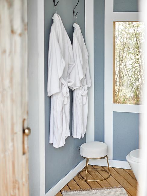 petite salle de bain bleue avec peignoirs blancs accrochés
