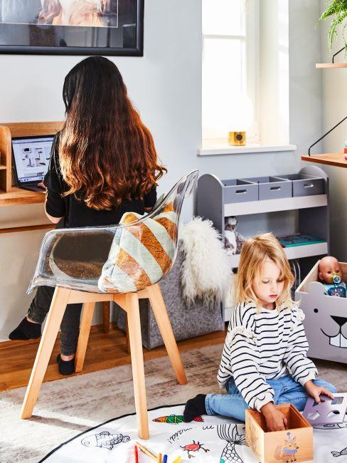 une femme assise devant son portable au bureau à domicile, une petite fille en train de jouer par terre, occuper ses enfants à la maison