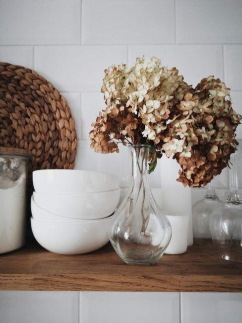 Bouquet de lilas séchées dans un vase transparent avec vaiselle blanche