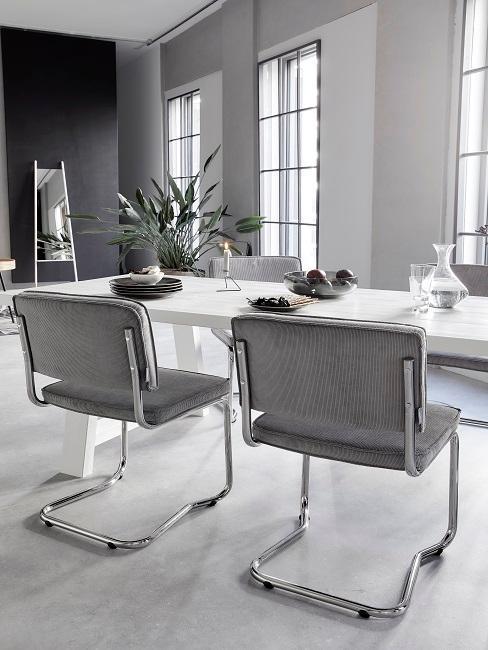 Salle à manger grise et blanche avec des grandes fenêtres