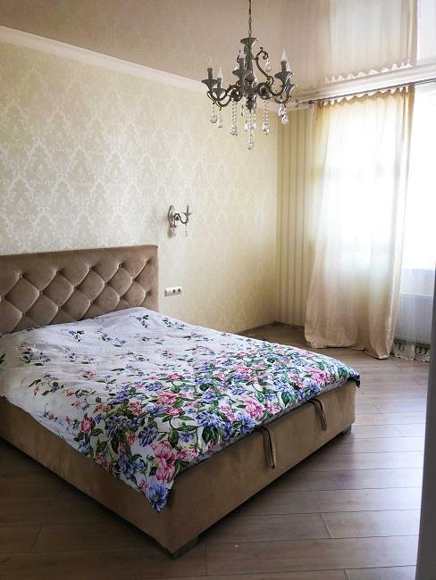 Chambre vintage couvrelit à fleurs et lustre