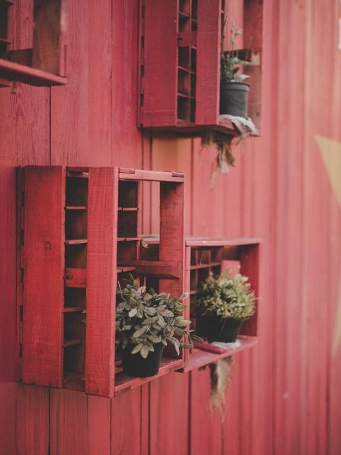 Mur extérieur en bois rouge avec déco de jardin récup réalisée avec des palettes décoratives et plantes