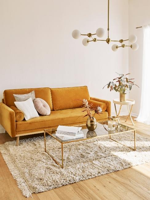 Table basse ne verre et bordures dorées dans salon avec fauteuil orange