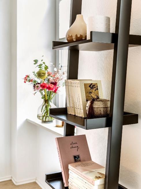 Etagère noire contre mur avec livres et plantes