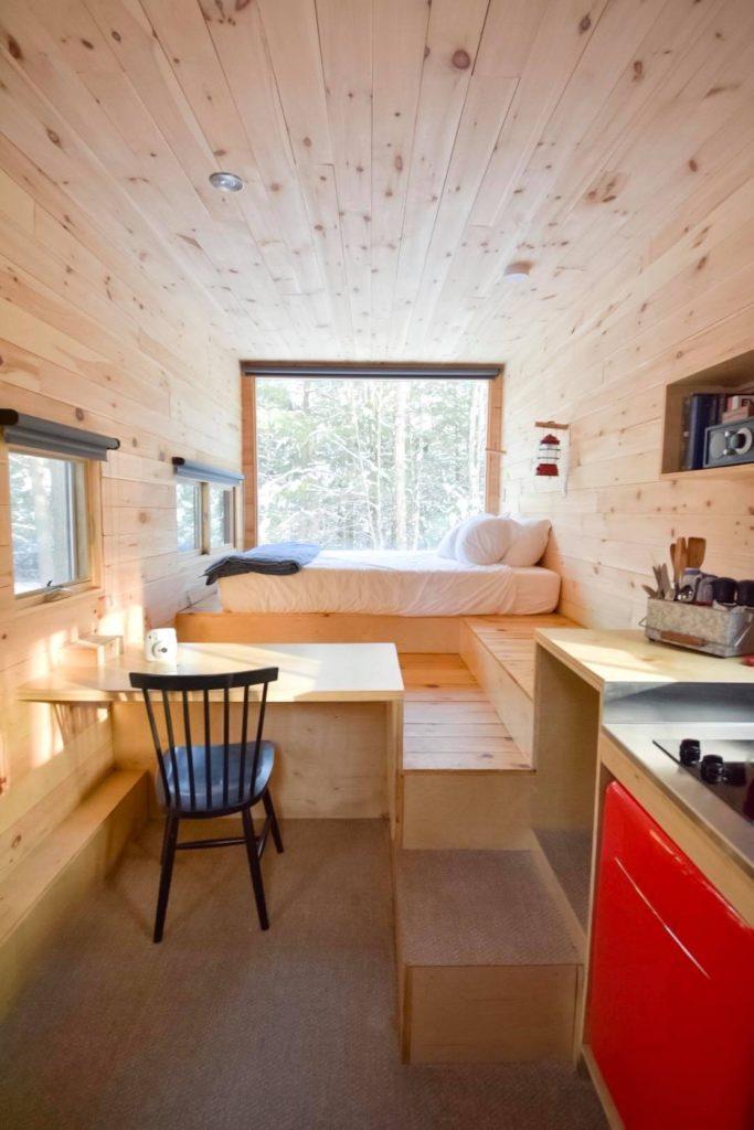 Petite maison fonctionnelle en bois avec lit en face de fenêtre