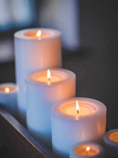 3 bougies allumées dans des porte-bougies blancs