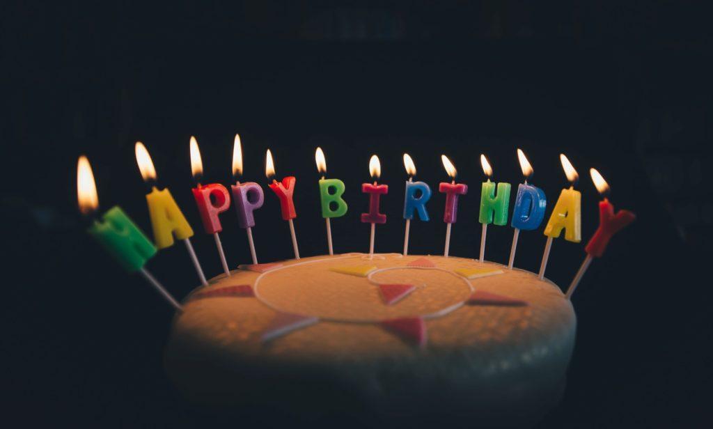 bougies happy birthday allumées sur un gâteau