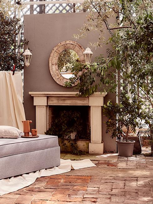 jardin d'hiver avec miroir accroché à un mur, fausse cheminée et plantes
