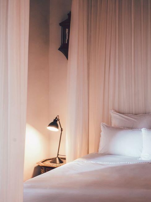 Chambre à coucher tons rose avec une lampe à poser lumière douce