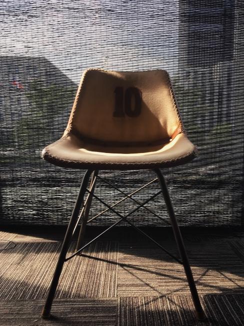 chaise design en cuir brun avec pied en métal noir