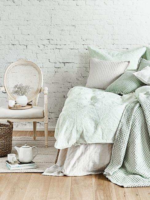 Chambre rustique chic avec parure de lit vert pastel et chaise blanche en bois