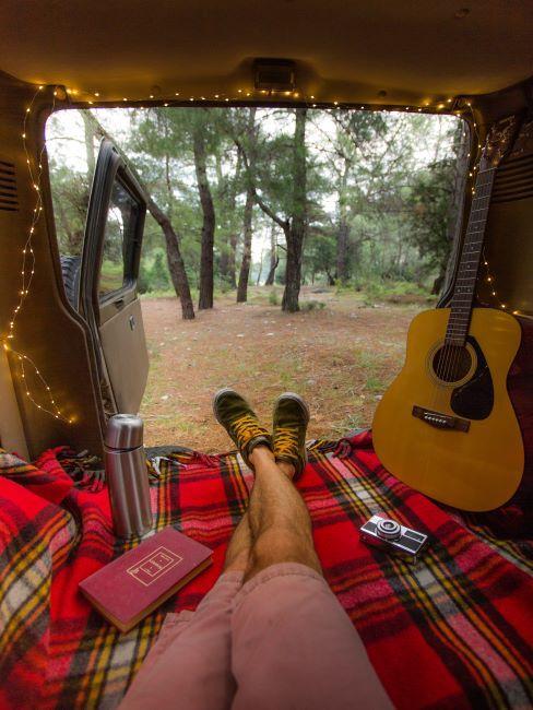 Personne assise sur plaid tartan rouge et noir avec guitare dans une voiture en forêt