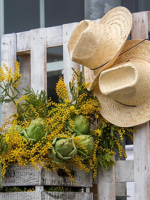 étagère réalisée à partir de palette avec des fleurs et des chapeaux