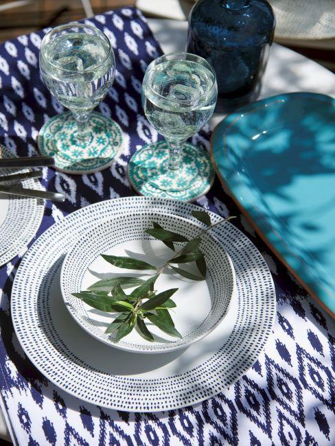 Table dressée avec vaisselle blanche et nappe à imprimé bleus et blancs
