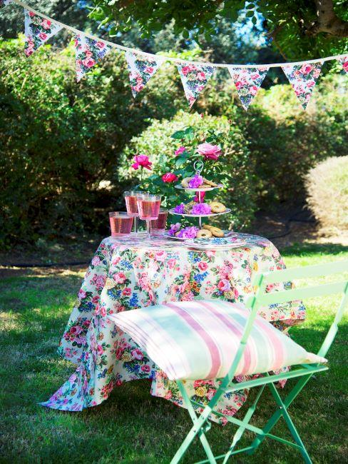 Jardin avec petite table habillée d'une nappe fleurie