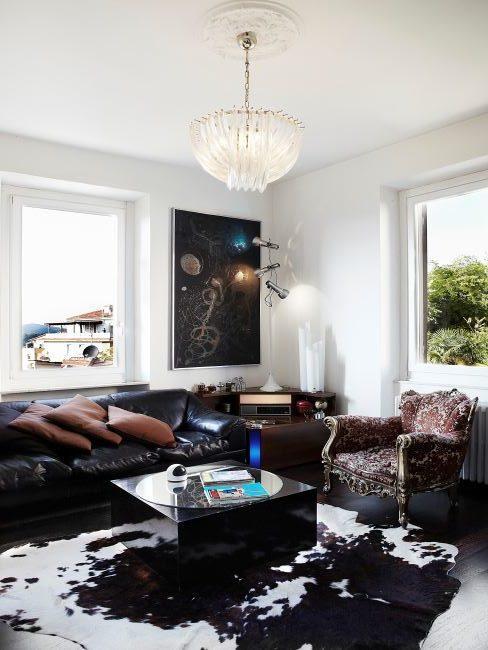 Salon avec canapé en cuir, fauteuil vintage et tapis en peau de vache