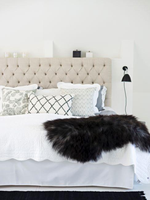 Peau de mouton anthracite jetée sur lit à sommier tapissier crème