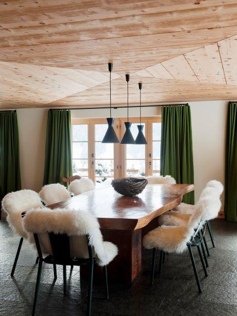 Salle à manger avec rideaux verts et chaises avec peaux de mouton crème