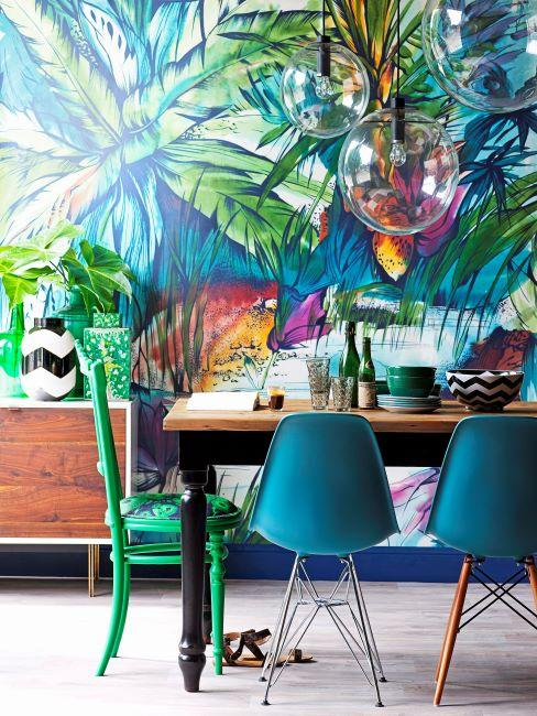 Salle à manger avec papier peint tropical multicolore, table en bois massif et chaise bleues