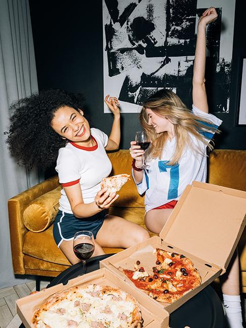 2 filles entrain de manger de la pizza et de faire la fête