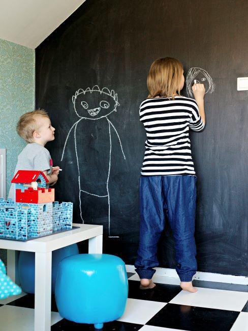 Deux petits garçons en train de dessiner sur un mur fait d'un grand tableau noir