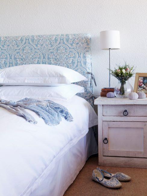 Lit avec tête de lit à imprimé bleu et table de chevet vintage couleur crème