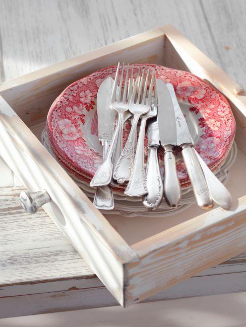 assiettes élégantes à bord orné à motif rouge, avec ménagère argentée posée dessus