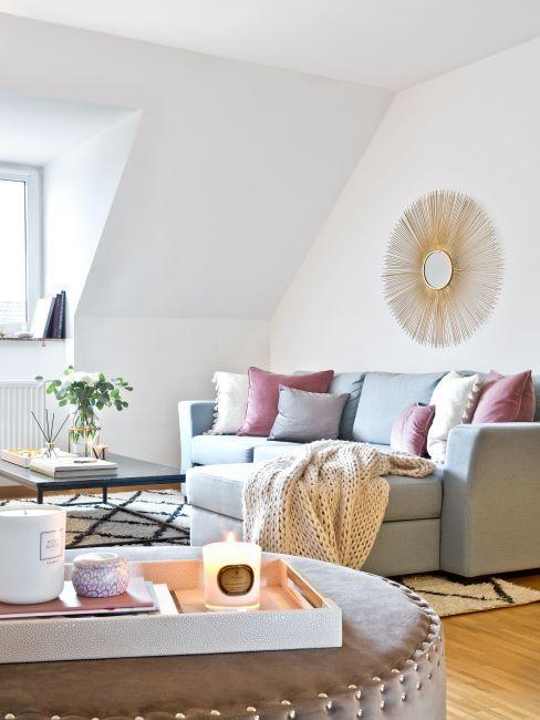 Séjour clair avec murs blancs et canapé avec méridienne gris clair, décoré des coussins et d'un plaid