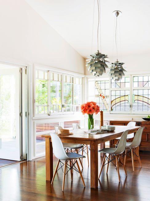 Salle à manger aux murs crème, à plafond haut, suspensions originales, vitres en verre teinté, table et chaises en bois