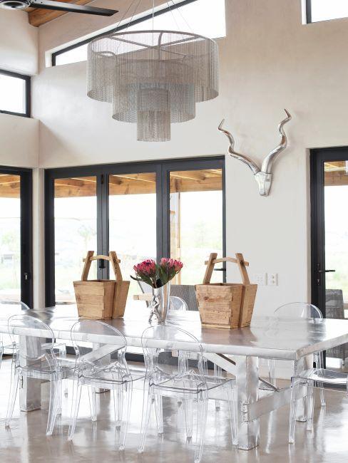 Salle à manger avec grande table en bois blanc et des chaises en plexi moderne