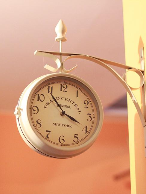 horloge gare en métal accroché à un mur jaune pastel
