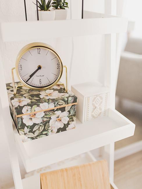 horloge dorée style vintage posée sur une boite avec des motifs floraux